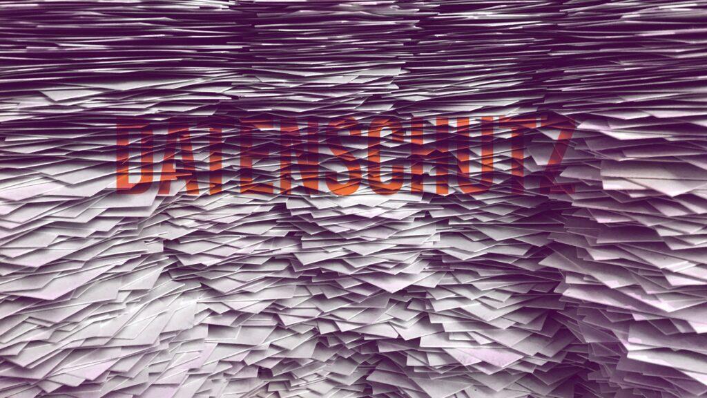 Ein Papierberg, darunter schwer lesbar, das Wort Datenschutz.